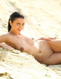 Naked girl Macy with nice tits and big areolas looks hot on the beach